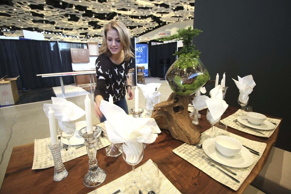 Kelsey Kosman of Dollhouse Design sets up her booth at the Winnipeg Renovation Show at the RBC Convention Centre Thursday. (Jessica Botelho-Urbanski / Winnipeg Free Press)