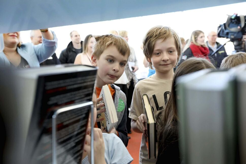 Students from Ecole Howden School shelve books -- instead of cutting ribbon -- to officially open the new Windsor Park Library. (Ruth Bonneville / Winnipeg Free Press)
