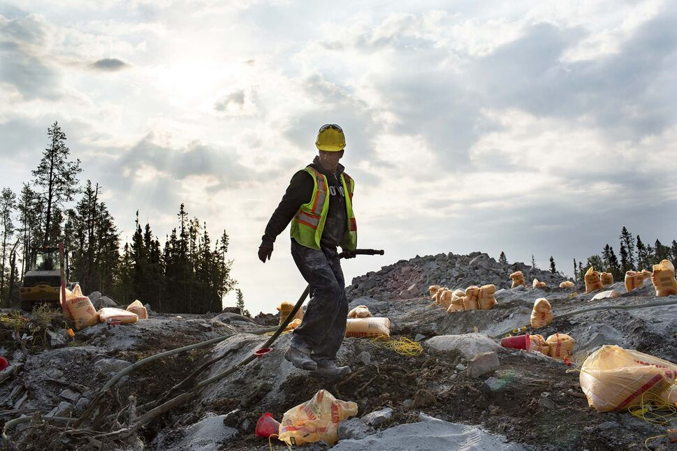 Jim Sinclair hauls a water pump hose amongst bags of explosives on Aug. 26. (ANDREW RYAN / WINNIPEG FREE PRESS)