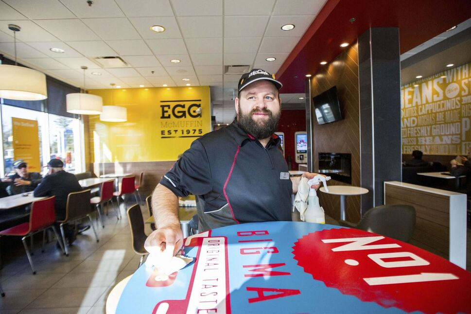 Edward Case, an adult living with special needs, cleans tables and mops floors at the McDonald's restaurant on Henderson Highway.
