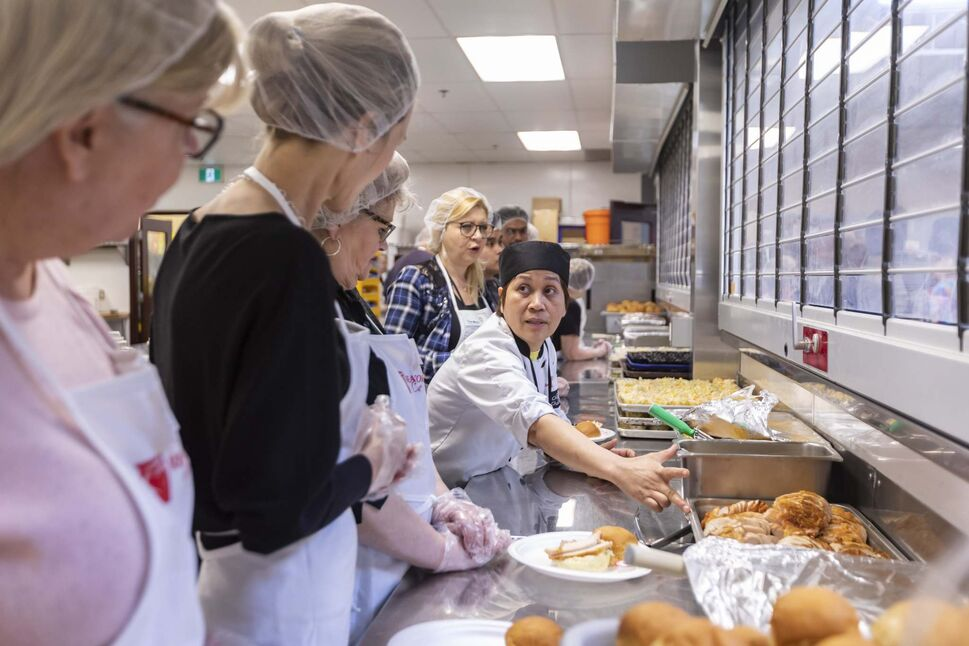 Volunteers help prepare and serve the annual Easter meal hosted by Siloam Mission on Monday.</p>