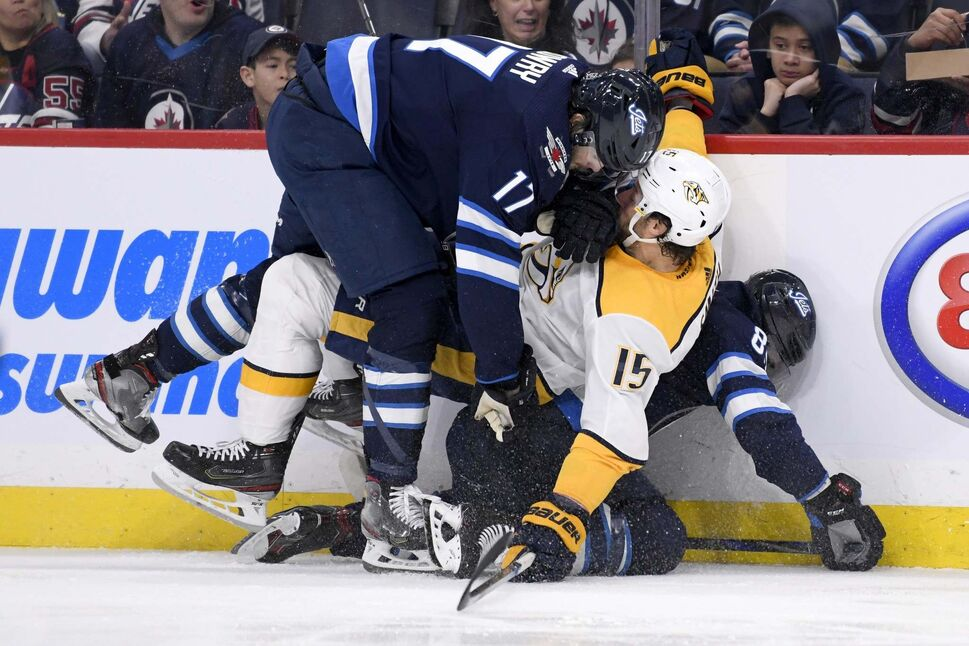 Winnipeg Jets Adam Lowry (17) and Mathieu Perreault (85) collide with Nashville Predators' Craig Smith (15) in Winnipeg on Sunday. (Fred Greenslade / The Canadian Press)