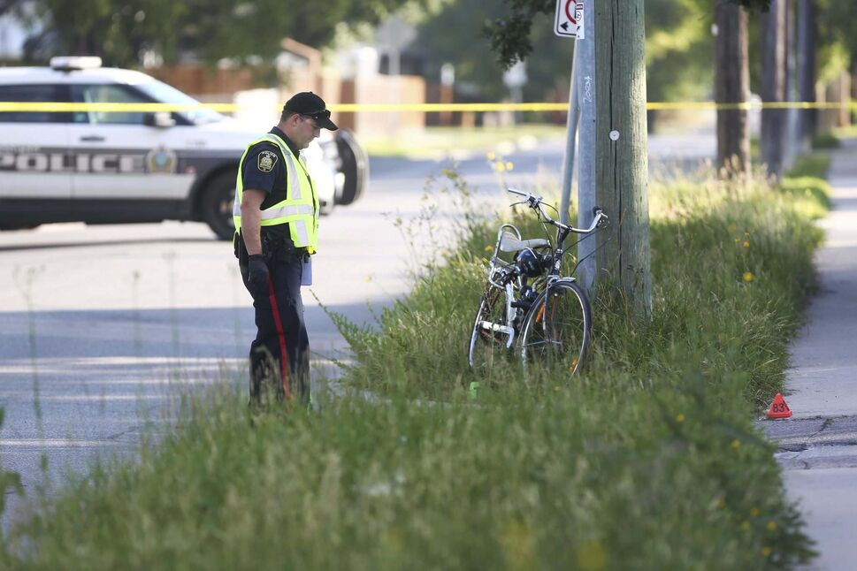 A Winnipeg police officer surveys the scene near Moncton Avenue and Grey Street after a cyclist was injured in a hit-and-run. The 50-year-old man died later in hospital. (MIKE DEAL / WINNIPEG FREE PRESS)