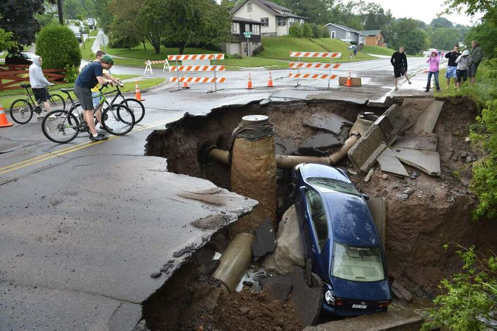 A car sits in a giant sinkhole in Duluth, Minn. Residents evacuated their homes and animals escaped from pens at a zoo as floods fed by a steady torrential downpour struck northeastern Minnesota. (AP Photo/The Star Tribune, Brian Peterson)
