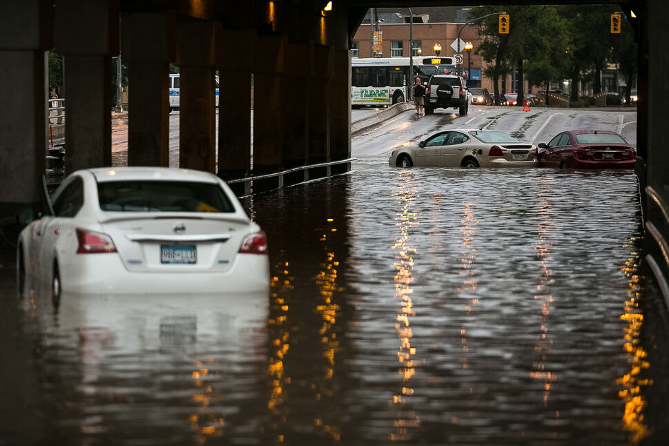 Abandoned cars at the flooded underpass at Higgins and Main Street after at least 50 mm and up to 65 mm of rain fell in a short period of time around 8 p.m. Aug. 21, 2014. The storm flooded underpasses and streets — especially in the south end of  Winnipeg.   (Melissa Tait / Winnipeg Free Press)