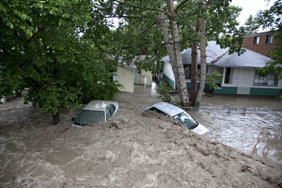 Submerged cars sit in the flood waters in High River, Alta. on June 20, 2013 after the Highwood River overflowed its banks.  Calgary and most of southern Alberta are being hammered by rain that has washed-out roads and bridges, caused mudslides and closed major highways. (Jordan Verlage / The Canadian press)