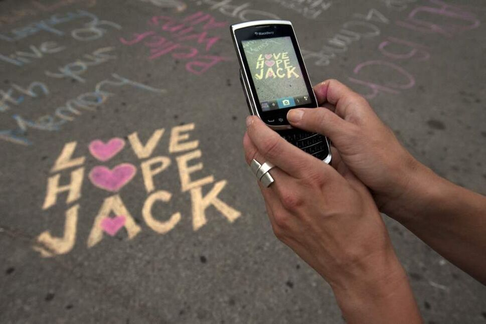 NDP MLA Sharon Blady takes a picture of her message at a memorial  in downtown Winnipeg for Jack Layton one year after his death. August 22, 2012 (COLE BREILAND / WINNIPEG FREE PRESS)