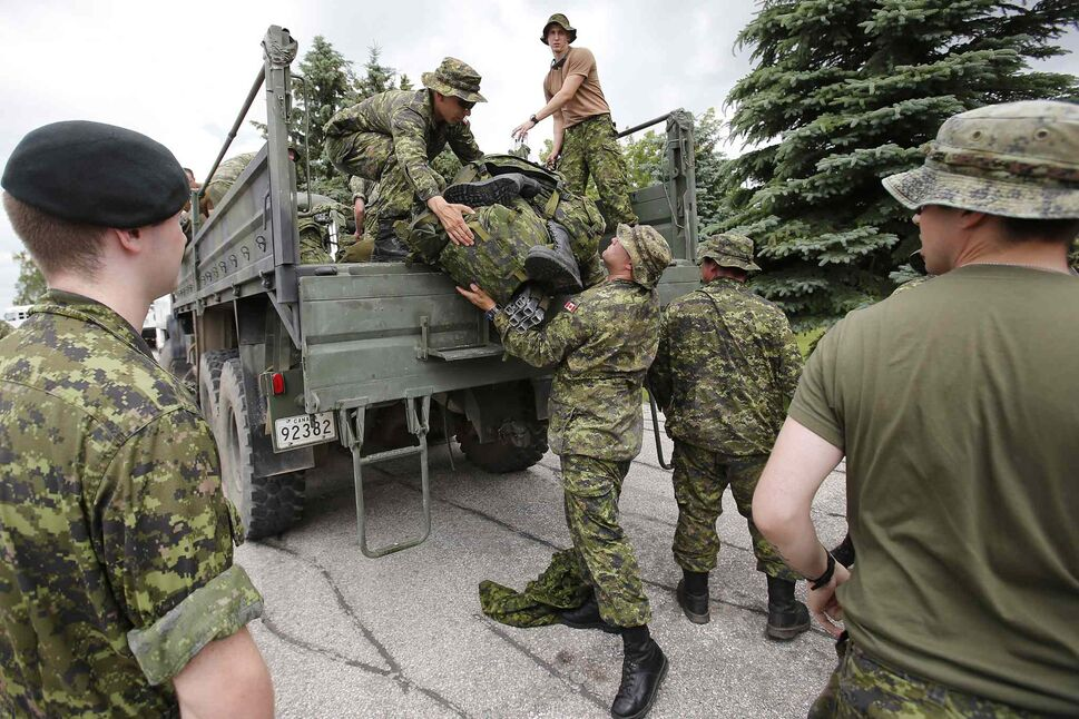 Military reserves arrive at Southport, Man. Saturday to assist with flood preparation. (John Woods / The Canadian Press)