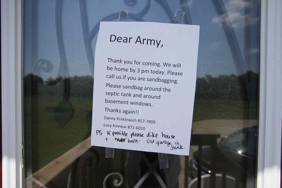 A sign taped to a door just south of the Hoop and Holler Bend, Man. welcomes the military Saturday.  (CP)
