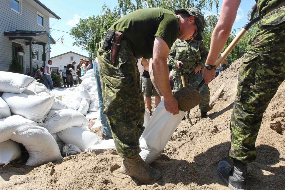 Soldiers from CFB Shilo and volunteers fill sandbags to protect Kevin Van Camp's home from flood waters near St. Francois Xavier Sunday afternoon. (Mike Deal / Winnipeg Free Press)