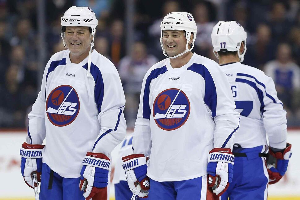 Former Winnipeg Jets Dave Ellett, left, and Dale Hawerchuk take a breather during a practice for the NHL's Heritage Classic Alumni Game in 2016. (John Woods / The Canadian Press files)
