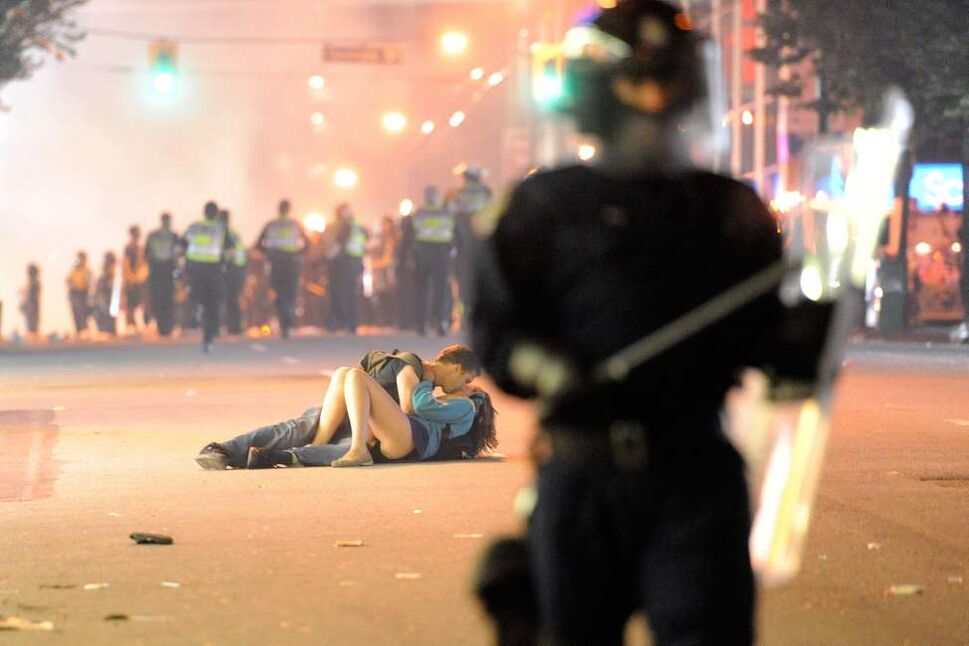 Riot police walk in the street as a couple kiss on June 15, 2011 in Vancouver, Canada. Vancouver broke out in riots after their hockey team the Vancouver Canucks lost in Game Seven of the Stanley Cup Finals.  (Photo by Rich Lam/Getty Images)