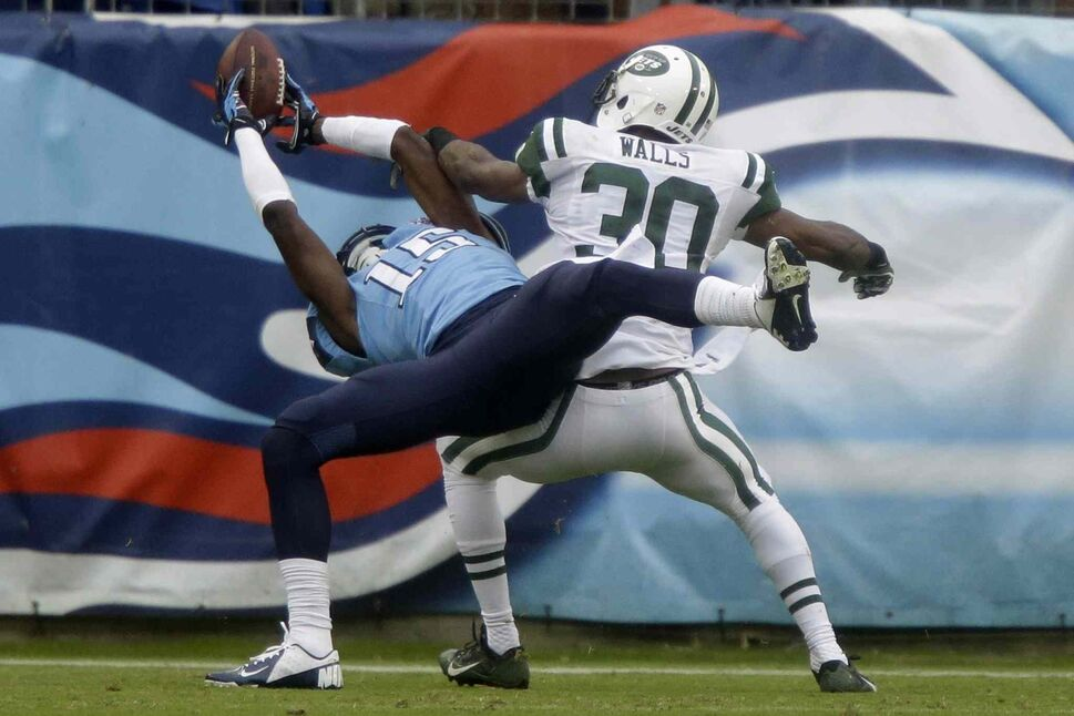 Tennessee Titans wide receiver Justin Hunter (left) catches a 16-yard touchdown pass as he is defended by New York Jets cornerback Darrin Walls during the Titans 38-13 victory Sunday in Nashville. (Wade Payne / The Associated Press)