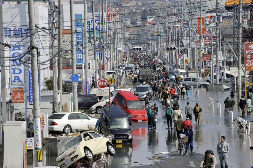 People walk on a tsunami-affected street in Ishinomaki, Miyagi Prefecture, northern Japan, Sunday March 13, 2011, two days after a powerful earthquake-triggered tsunami hit the country's east coast. (AP Photo/Kyodo News)