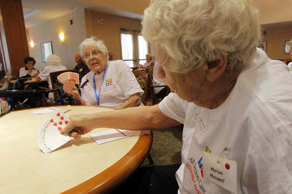 Marion Maxwell (right) lays her cards on the table at the All Senior Care Senior Games 2014.   (Boris Minkevich / Winnipeg Free Press)