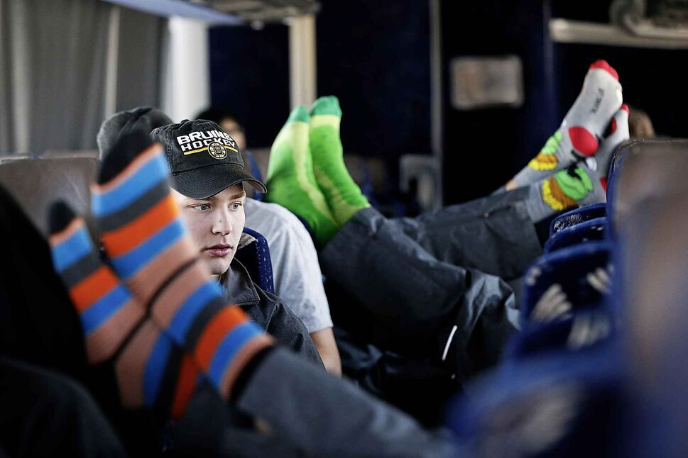 Pistons forward Max Neill looks around as other players relax during the bus ride.</p>