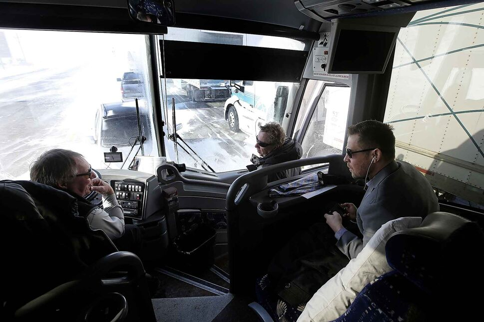 Hamelin and Pistons head coach Paul Dyck get advice from another bus driver as they wait for 3.5 hours in Headingley for the road to open.</p>