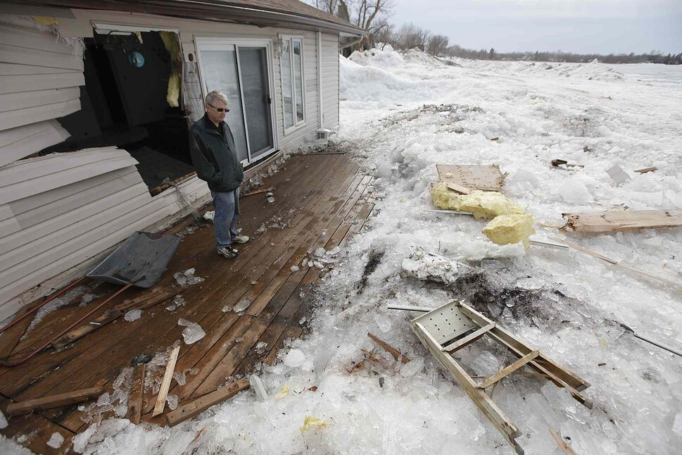 On Sunday May 12, 2013, after clearing snow piled to the roof with his sons Lorne Perche, looks over the destruction at his cottage on Ochre Beach after the lake ice was blown ashore by strong winds the day prior. (John Woods / Winnipeg Free Press)