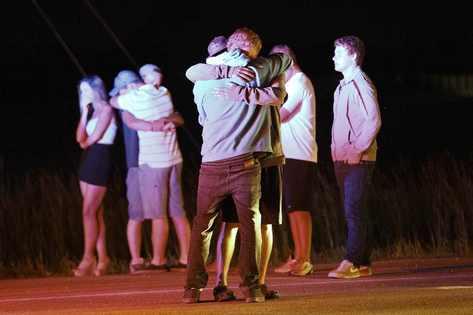 People comfort each other at the scene of a head-on collision between a pickup truck and a semi on the Trans Canada in Headingley July 22, 2013. The male driver of the pickup died at the scene. (John Woods / Winnipeg Free Press)
