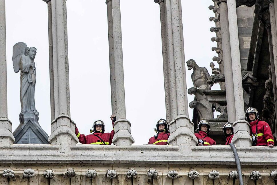 Fire fighters are seen in a tower of Notre Dame cathedral. (Christophe Petit Tesson / The Associated Press)