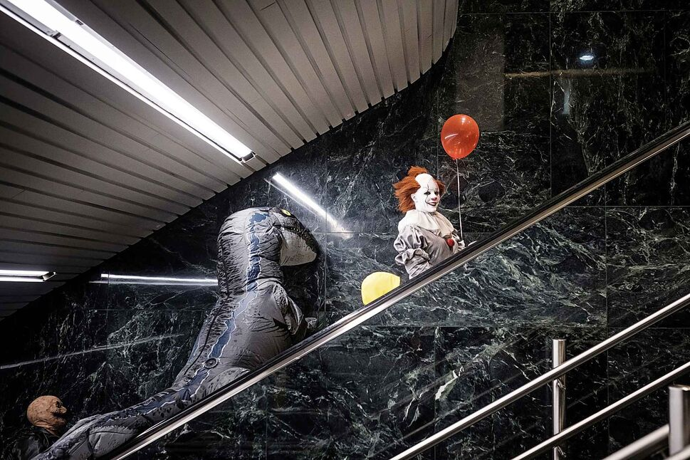 DANIEL CRUMP / WINNIPEG FREE PRESS</p><p>October 27 — Pennywise the clown and a dinosaur ride an escalator to the third floor of the Winnipeg Convention Centre. A sight that might not make much sense anywhere else is perfectly common place at C4 Comic-Con.</p>