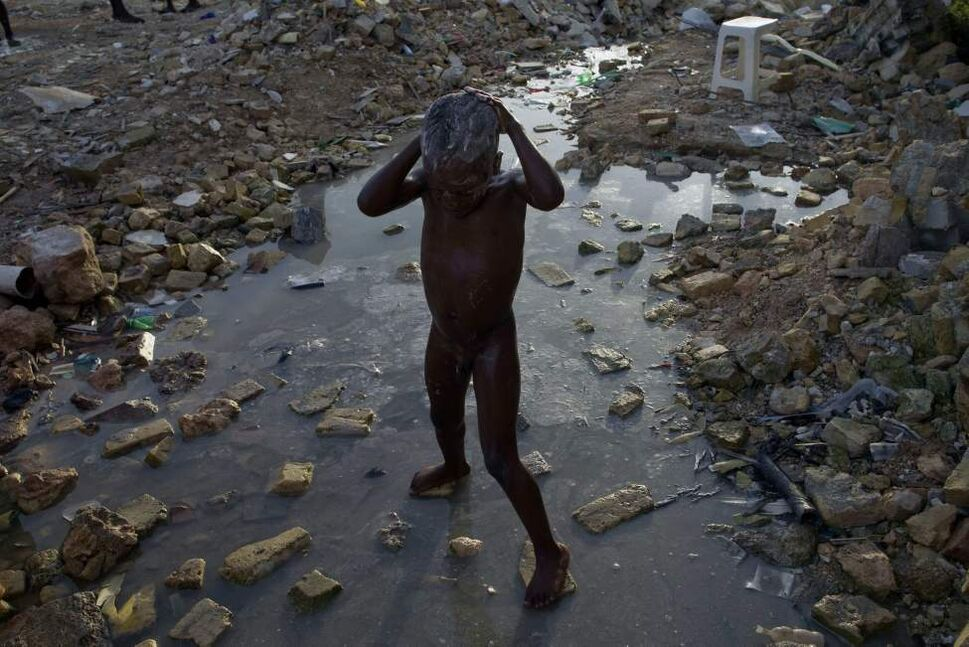 A child bathes in a puddle of water on the ruins of a house destroyed by the Jan. 12 earthquake In Port-au-Prince, Haiti, Monday, Aug. 23, 2010.  (Ramon Espinosa / The Associated Press)