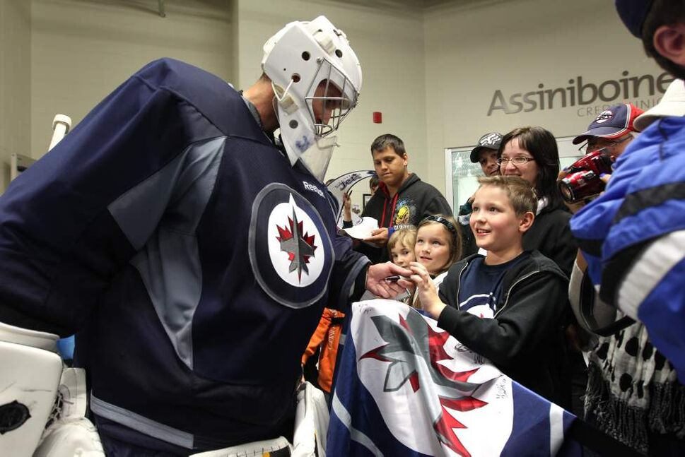 Brendan Hrushka gets his flag signed by one of his favorite Jets goalies (from Group C). (RUTH BONNEVILLE / WINNIPEG FREE PRESS)