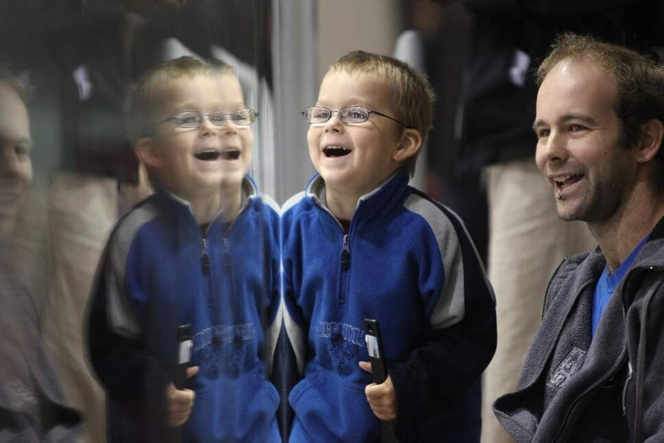 Four-year-old Alain Geal enjoys watching the players on the ice with his dad, Mike, Saturday.