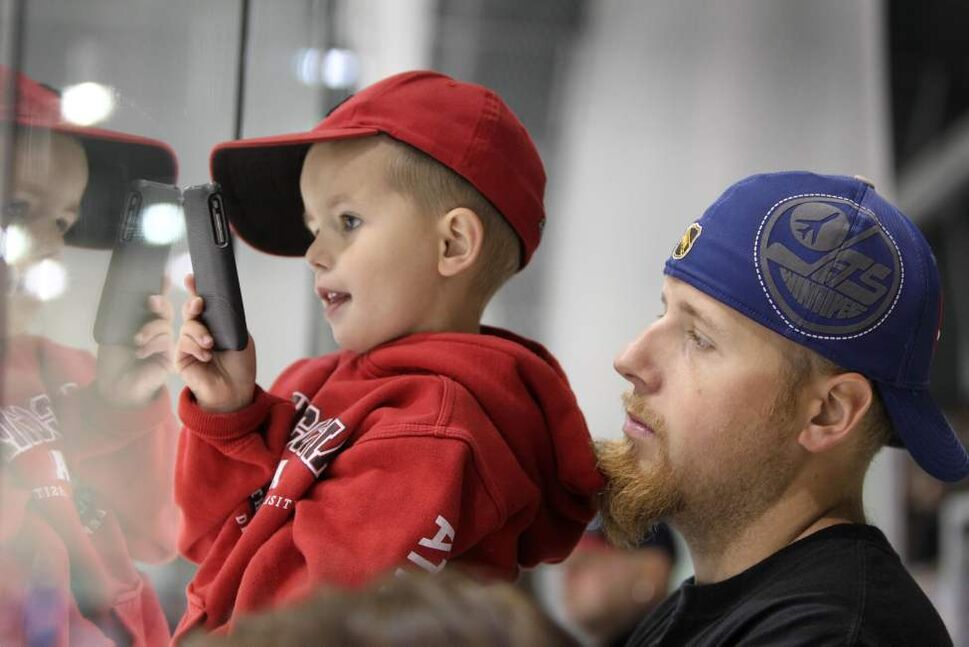 A dad holds his son up to the glass to take a picture Saturday. (RUTH BONNEVILLE / WINNIPEG FREE PRESS)