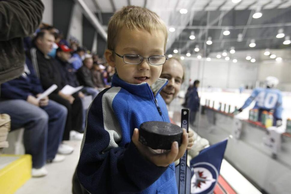 Four year old Alain Geal looks at a puck he grabbed after it flew over the glass. (RUTH BONNEVILLE / WINNIPEG FREE PRESS)