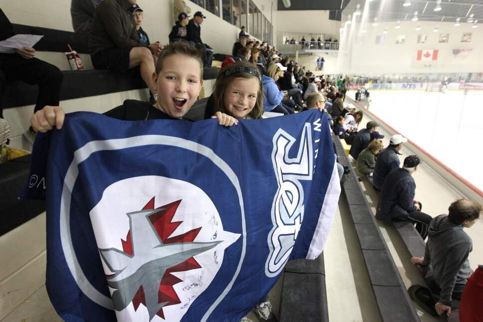 Brendan Hrushka, 12, and his sister Claire, 9, hold up their flag as they cheer on the Group C team as they practice on the ice. (RUTH BONNEVILLE / WINNIPEG FREE PRESS)