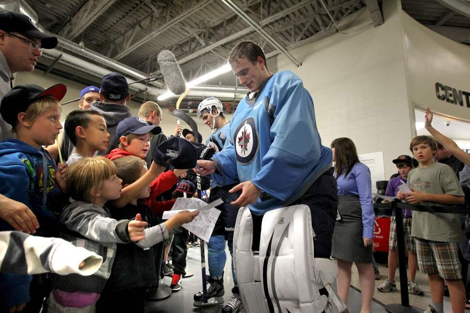 Chris Carrozzi signs some papers after Saturday's practice. (RUTH BONNEVILLE / WINNIPEG FREE PRESS)