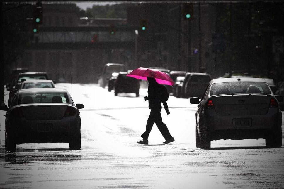 A person carrying a shocking pink umbrella crosses St. Mary at Smith in the middle of a sun shower in Winnipeg. September 3, 2011 (John Woods/Winnipeg Free Press)