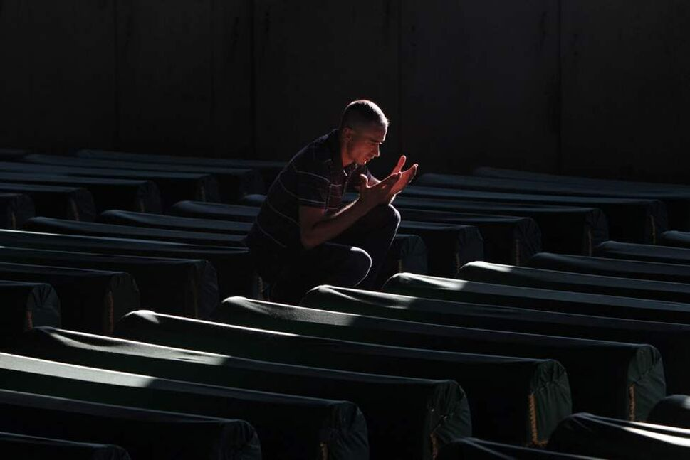 A Bosnian Muslim man prays near the coffin of a relative, among 520 newly identified Srebrenica victims, at the Potocari memorial cemetery near Srebrenica. The 520 victims will be buried at a memorial centre on the 17th anniversary of the massacre of 8,000 men and boys, defined by the International Court of Justice as genocide. (AP Photo/Amel Emric)