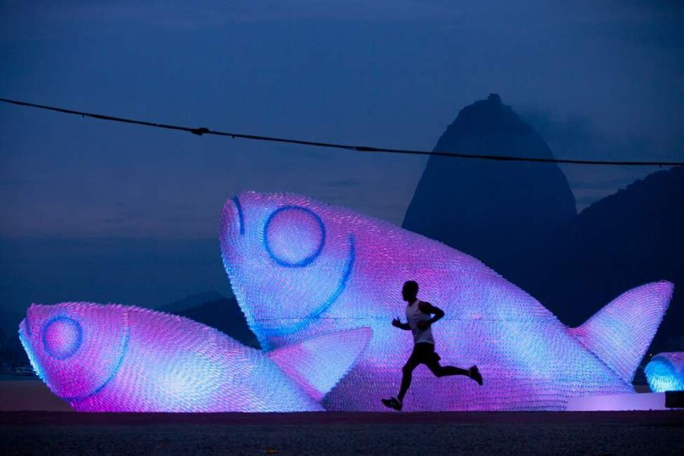 A man runs on Botafogo beach near a huge sculpture made from plastic bottles, backdropped by a silhouette of Sugarloaf mountain in Rio de Janeiro, Brazil, in the early morning hours Wednesday. (AP Photo/Felipe Dana)
