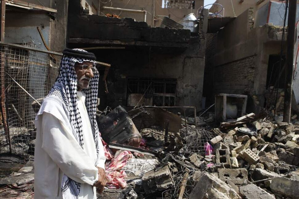 A man stands in front of the scene of a bomb attack in Madain, southeast of Baghdad, Iraq. An onslaught of bombings and shootings killed scores of people across Iraq on Monday, in the nation's deadliest day so far this year. The attacks come days after the leader of al-Qaida in Iraq declared a new offensive seeking to re-assert its might in the security vacuum left by the departing Americans. (AP Photo/Karim Kadim)