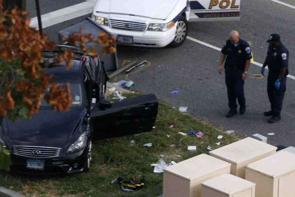 Capitol Hill police officers inspect a vehicle after the collision and shooting. (Charles Dharapak / The Associated Press)