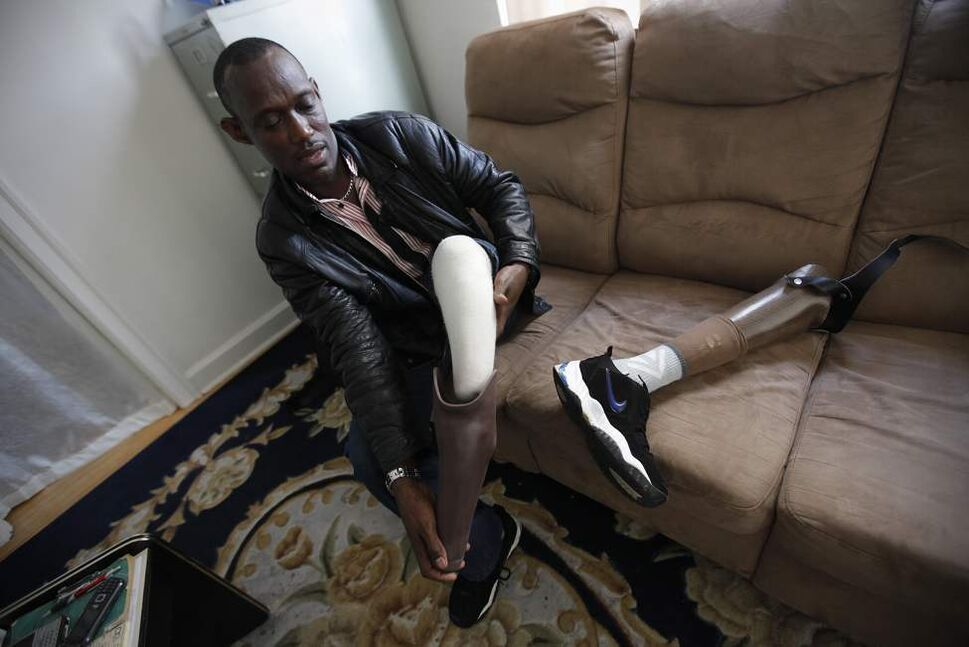 Cyrilo Simpunga, a recent refugee from the Congo, is photographed putting on his artificial leg in his downtown apartment in Winnipeg Monday June 12, 2012. Simpunga had his left leg cut off during the Congo civil war in 2004. (John Woods / Winnipeg Free Press)