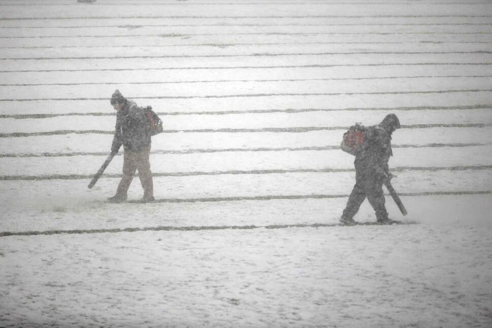 Philadelphia Eagles personnel clear snow from the field before Sunday's game between the Philadelphia Eagles and the Detroit Lions. (Matt Rourke / The Associated Press)