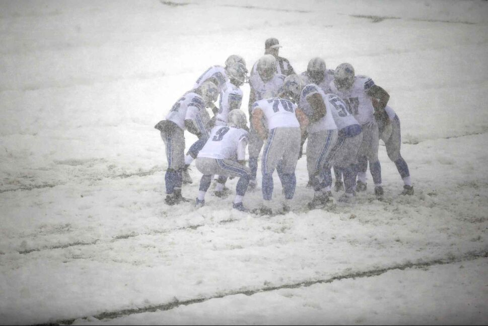 The Detroit Lions huddle during a snowstorm in the first half. (Matt Rourke / The Associated Press)