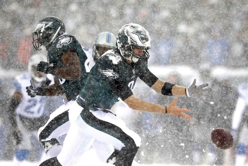 Nick Foles (centre) of the Philadelphia Eagles can't hang on to the ball during the first half of the game against the Detroit Lions. (Michael Perez / The Associated Press)