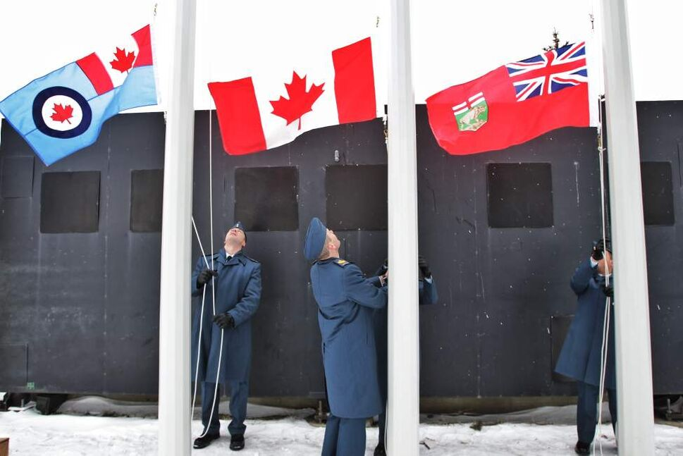 Members of the Royal Canadian Air Force flag group raise the flags during the singing of the national anthem at the sign dedication at the entrance/exit to the James Armstrong Richardson International Airport on Wellington Avenue.   Thursday, November 29, 2012. (MIKE DEAL / WINNIPEG FREE PRESS)