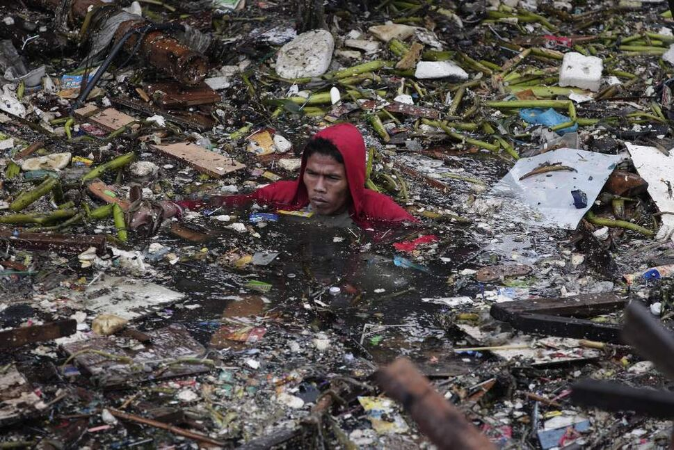 A Filipino resident swims in polluted waters as he tries to salvage items from their house after two empty barges rammed into shanties on stilts at a poor community in Manila, Philippines on Monday July 30, 2012. A tropical storm roughed up seas and dumped torrents of monsoon rains in central and the northern Philippines, leaving at least three people dead and causing barges to smash into dozens of shanties along Manila Bay, officials said Monday. AP Photo / Aaron Favila