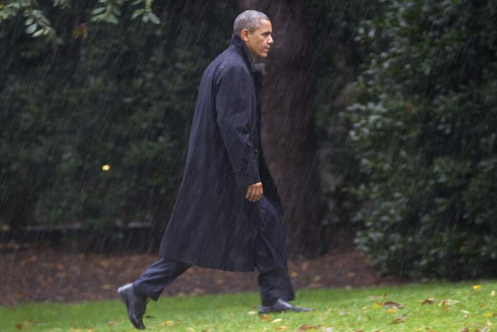 After canceling his appearance at a morning campaign rally in Orlando, Fla., President Barack Obama walks toward the White House in a driving rain after returning to Washington to monitor preparations for early response to Hurricane Sandy. (AP Photo/Jacquelyn Martin)