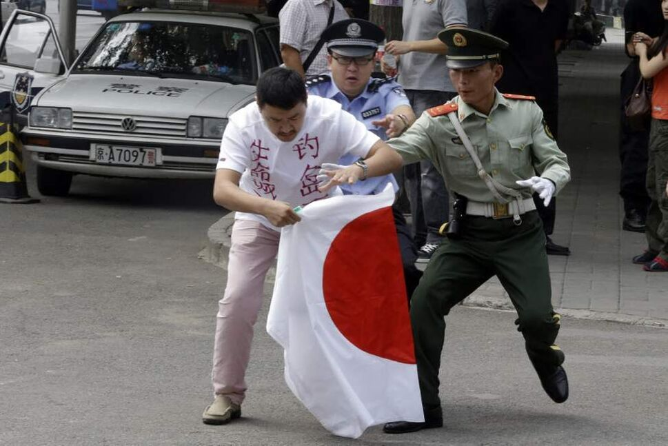 Chinese security personnel try to stop a Chinese man as he prepares to burn Japanese national flag outside the Japanese embassy in Beijing, China. Chinese government ships are patrolling near contested East China Sea islands in a show of anger after Tokyo moved to assert its control in the area. Beijing warned Monday, Sept. 10, 2012 that Japan would suffer unspecified consequences if Tokyo purchased the islands from private owners, as it formally did Tuesday. (AP Photo/Ng Han Guan)