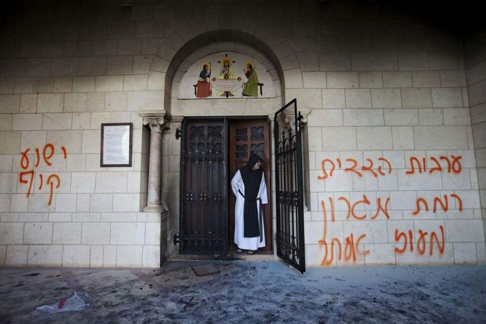 A catholic monk stands in a doorway of the Latrun Trappist Monastery where Israeli police say vandals spray-painted anti-Christian and pro-settler graffiti and set the monastery's door on fire, in Latrun, between Jerusalem and Tel Aviv, Israel. Suspicion fell on Jewish settlers and their supporters who retaliate against anti-settlement measures, generally by attacking Palestinian property, but also by vandalizing Christian sites and Israeli military facilities. (AP Photo/Oded Balilty)