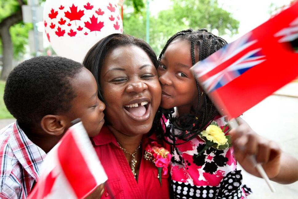 Meta Nana Tshiovo gets kisses from her daughter Marie-Rose Mpidi, 7, while her son Rachie, 5, after Meta and her daughter became Canadian citizens Friday morning at Knox United Church. The family celebrated with friends and family with balloons and flags next to Central Park. Canada Day.