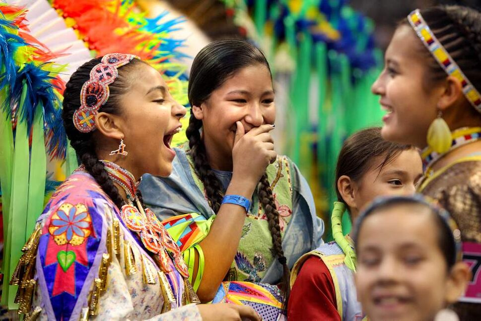 (l-r) Waskwane Stonefish, 13, Oke-Twisha Robert , 12, and Lilia Kingbird,15, giggle and laugh as they start to dance in the Grand Entry Pow Wow at MTS Centre Saturday Night.  The Pow Wow was part of the Manito Ahbee Celebration over the weekend.   