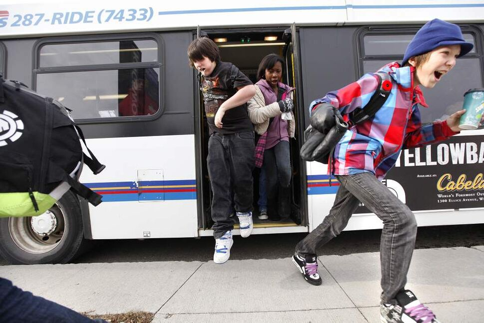 Grade 7 Windsor School students Garret (right) and Julian (middle) race off the transit bus heading back to school after shops class Tuesday. 