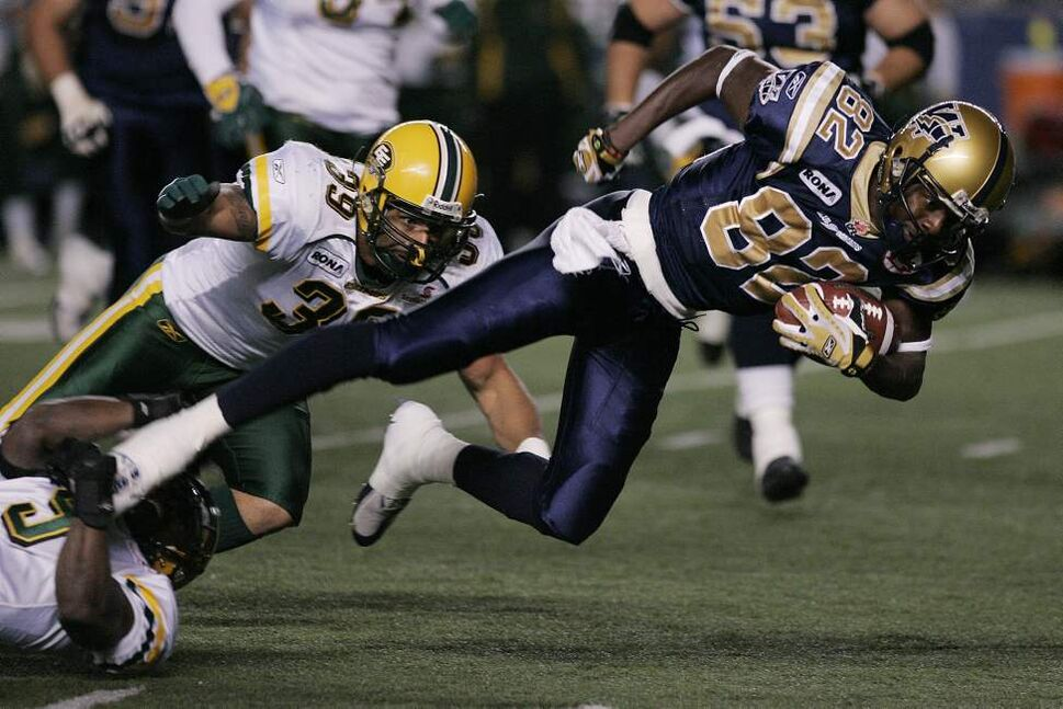 Winnipeg Blue Bombers' Terrence Edwards (82) gets tackled by Edmonton Eskimos' Lenny Williams (9) and Agustin Barrenechea (39) in the first half of their CFL game in Winnipeg Friday, September 26, 2008.   THE CANADIAN PRESS/John Woods